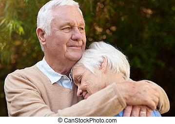 Romantic senior man warmly hugging his woman outside