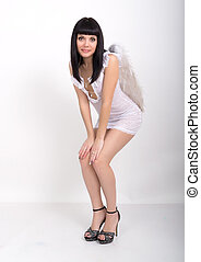 Romantic sensual Sexy slender brunette in a little white dress on high heels with wings on his back.