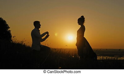 Romantic Silhouette of Man Getting Down on his Knee and Proposing to Woman on high hill - Couple Gets Engaged at Sunset - Man Putting Ring on Girl's Finger, slider shot