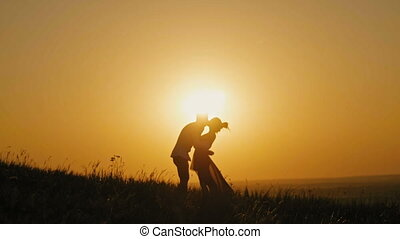 Romantic Silhouette of Man on high hill - at Sunset - kissing and dancing slow motion