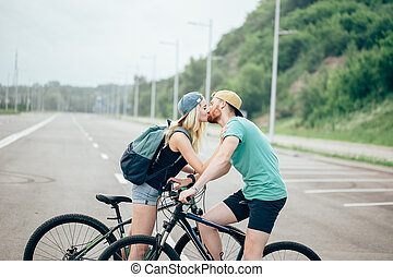 Romantic sports couple kissing against blurred background with bicycles