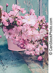 Romantic Spring background with a vase of Japanese cherry...