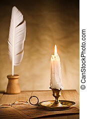 Romantic still-life with burning candle and music sheet