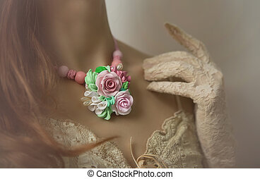 Romantic style: Fashion studio shot of beautiful woman with a floral necklace (jewelery made of polymer clay)