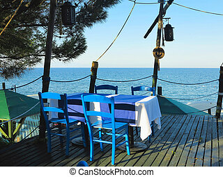Romantic table for two in the restaurant on sea background