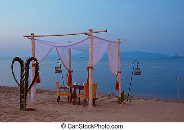 Romantic table setting on the beach at dusk