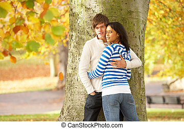Romantic Teenage Couple By Tree In Autumn Park