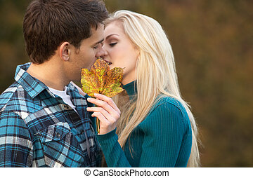 Romantic Teenage Couple Kissing Behind Autumn Leaf