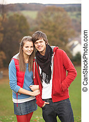 Romantic Teenage Couple Walking Through Autumn Landscape