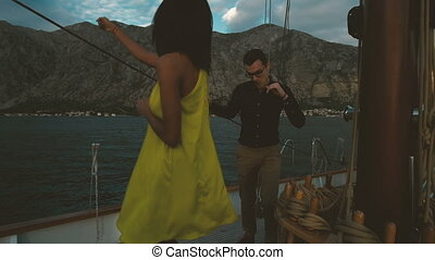 Romantic traveling of loving couple dancing on yacht outdoors