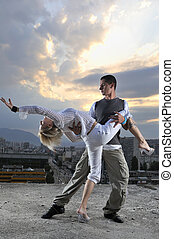 romantic urban couple dancing on top of the bulding