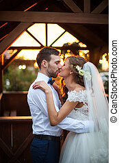 Romantic valentynes couple of newlyweds hugging at kissing at sunset near a wooden house