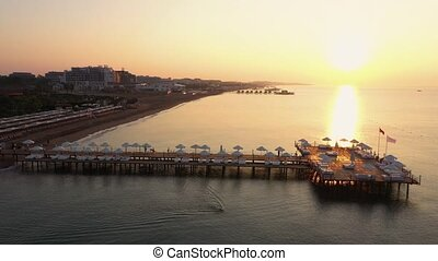 Romantic view of the pier at sunset. Top view of sea, beach ...