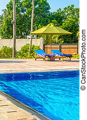 Romantic view of two sunbeds at swimming pool
