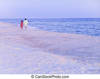 Romantic walk - Couple walk along the beach holding hands