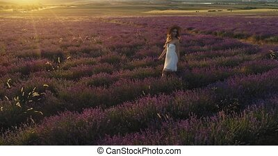 Romantic walk of woman through the field of lavender at sunset