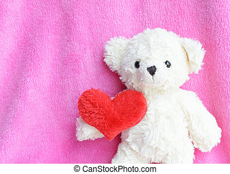 Romantic with teddy bear hand holding red heart on pink backgrounds
