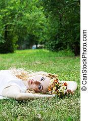 Romantic woman lying down on grass