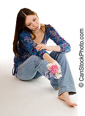 Romantic woman siting on the flor with flowers in hand