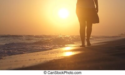 Romantic woman walking on the beach barefoot at sunset in...