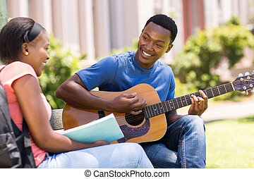 young african college student playing guitar for his girlfriend