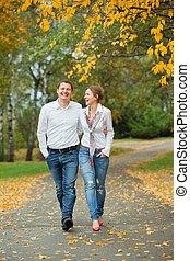 Romantic young beautiful couple on autumn walk