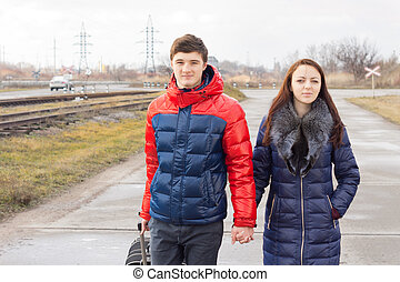 Romantic young couple carrying a suitcase