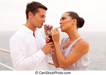 young couple drinking cocktail together