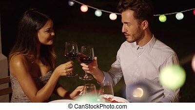 Romantic young couple enjoying dinner and wine