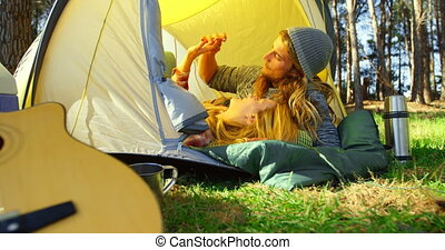 Romantic young couple holding hands in tent 4k