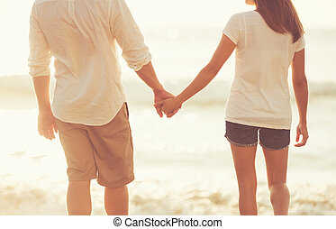 Young Couple Holding Hands on the Beach at Sunset
