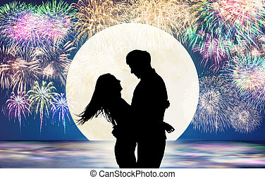 Romantic young Couple hug on the beach and fireworks background