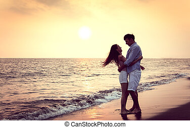 Romantic young Couple hug on the beach at sunset