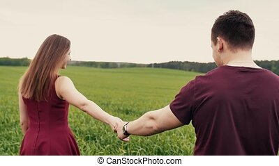Romantic young couple in love holding hands, walking in a field with long grass. Slow mo, steadicam shot