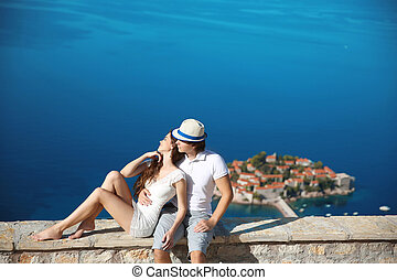 Romantic young couple in love over sea shore above Sveti Stefan island in Budva, Montenegro. Travel. Vacation. Family.