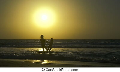 Romantic young couple is falling in love on the beach at sunset. Happy Man with woman is holding hands and circling on the shore of the sea in water. Two people in love, have fun under the sun.