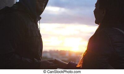 Romantic young couple is kissing on a sunset with sun shining bright behind them on a city horizon. Slow motion.