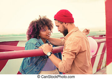 Romantic young couple looking at each other while standing on the roof