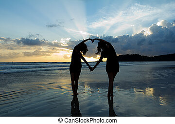 Romantic young couple making heart shape with arms on beach at sunset  beautiful sky.