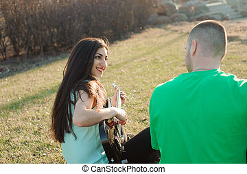Romantic young couple portrait playing guitar under blue sky.