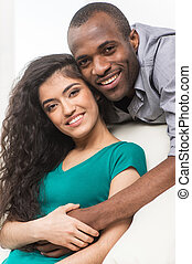 Romantic young couple relaxing on sofa. african man smiling and hugging indian woman