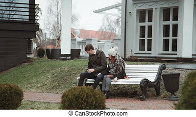 Romantic Young couple sitting on a white bench, in a coat and hat, cold weather, lifestyles
