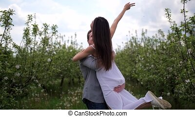 Romantic young couple spending leisure in orchard