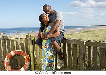 Romantic Young Couple Standing By Wooden Fence Of Beach Hut...