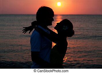 romantic young couple sunset silhouette on beach. honeymoon