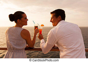 young couple toasting with cocktail on cruise