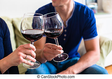 Romantic young couple toasting with red wine while sitting on th