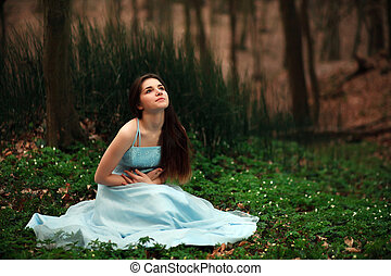 Romantic young girl in a long blue dress, in the twilight fairy