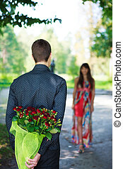 Romantic young man giving a bouquet of red roses to his girlfriend. Sunny park