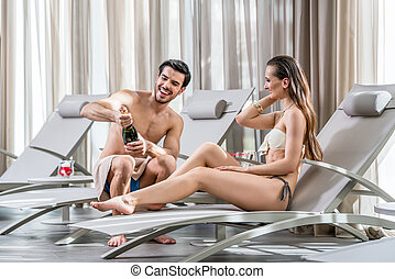Romantic young man opening a bottle of champagne while relaxing